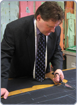 tailor David Kelly cutting fabric for a made-to-measure suit